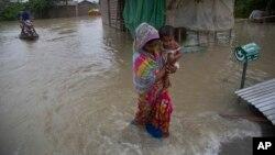 인도 아삼주 가우하티의 마을이 폭우로 인해 침수된 가운데 여성이 아이를 안고 대피하고 있다.