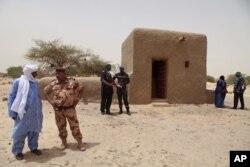 ຮູບນີ້ຖ່າຍເມື່ອວັນທີ 18 ກໍລະກົດ 2015, ພວກຄົນທີ່ເຂົ້າຮ່ວມ ໃນພິທີ ຢືນຢູ່ໃກ້ໆ ສາສະໜາສະຖ່ານ ທີ່ໄດ້ຖືກຟື້ນຟູຂຶ້ນໃໝ່ ຢູ່ໃນເມືອງ Timbuktu ຂອງ Mali.