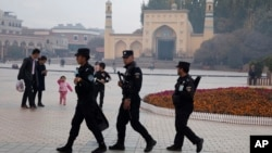 In this Nov. 4, 2017 photo, Uighur security personnel patrol near the Id Kah Mosque in Kashgar in western China's Xinjiang region. (AP Photo/Ng Han Guan)