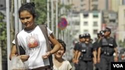 Seorang perempuan dan anaknya berjalan di depan polisi Tiongkok yang melakukan patroli di ibukota Xinjiang, Urumqi (foto: dok).