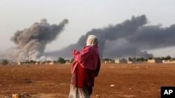 叙利亚库尔德人在叙利亚边境看空袭后升起的浓烟