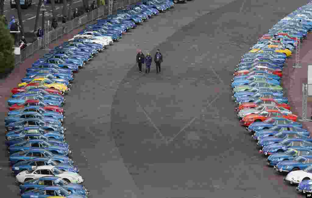 People walk between old Alpine Renault Berlinettes during the official presentation of the new Alpine Renault Vision auto by chairman and CEO of Renault Carlos Ghosn in Monaco.