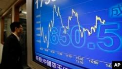 A man walk looks at the Hang Seng index at a brokerage in Hong Kong. Markets around the world have had sharp losses and gains because of worrying news about China's economy.