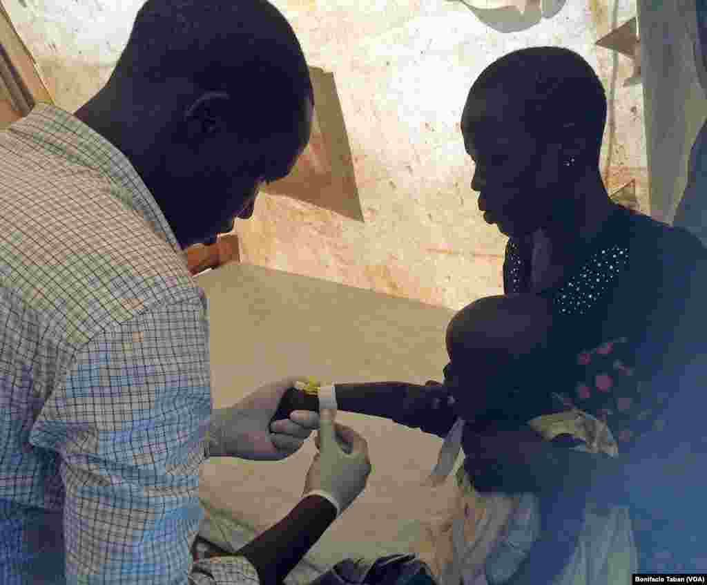 A health worker prepares to give medication intravenously to a South Sudanese child who has tested positive for malaria, in Ayilo refugee resettlement camp in Uganda