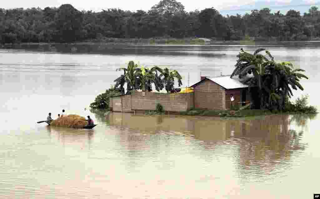 Indian villagers row through their flooded village in a small boat, in northeastern Assam state, India, Aug. 18, 2014.