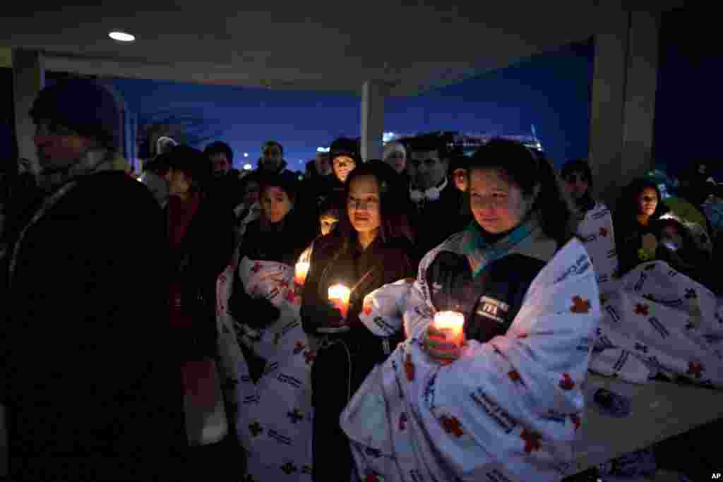 Residents hold a candlelight vigil outside Newtown High School after President Barack Obama delivered remarks at an interfaith vigil for the victims of the Sandy Hook Elementary School shooting, December 16, 2012.