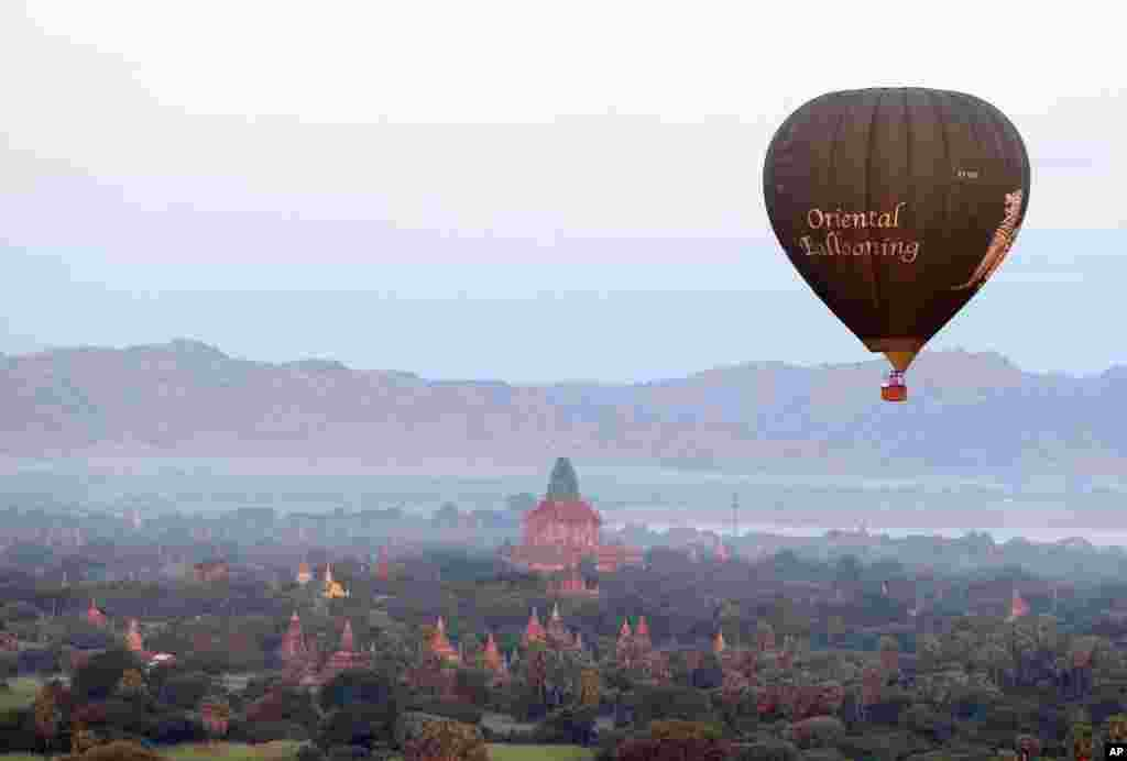 A hot air balloon flies over the Myanmar's ancient temples just before sunrise in old Bagan, Nyaung U district.