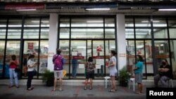 Warga Filipina mengantri di luar apotek, sehari sebelum Ibu Kota Filipina, Manila, kembali memberlakukan restriksi lebih ketat di tengah pandemi Covid-19, 3 Agustus 2020. (REUTERS/Eloisa Lopez)