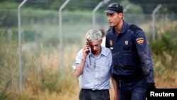 An injured man, identified by Spanish newspapers as the train's driver, Francisco Jose Garzon, is helped by a policeman after the crash near Santiago de Compostela, northwestern Spain, July 24, 2013.