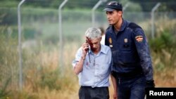 An injured man, identified by Spanish newspapers El Pais and El Mundo as the train driver Francisco Jose Garzon, is helped by a policeman after a train crashed near Santiago de Compostela, northwestern Spain, July 24, 2013.
