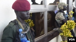 A rebel soldier (L) and a government soldier are seen keeping guard together at Juba International Airport before the return of former rebel leader Riek Machar on April 26, 2016. (J. Patinkin/VOA)