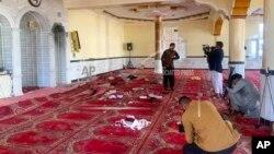 Sejumlah jurnalis memotret dan mengambil gambar di dalam sebuah masjid setelah ledakan di distrik Shakar Dara, di Kabul, Afghanistan, 14 Mei 2021. (Foto: Rahmat Gul/AP)