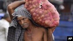 Một công nhân Ấn Độ vác bao khoai tây tại một kho hàng ở Jammu, Ânh Độ