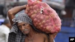 Một công nhân vác khoai tây tại một kho hàng ở Jammu, Ấn Độ