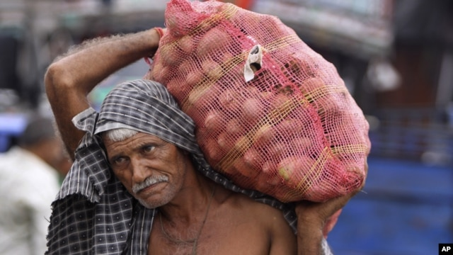 An Indian laborer carries a bag of potatoes at a warehouse in Jammu, India, July 31, 2012.