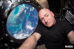 NASA astronaut Scott Kelly inside the cupola of the International Space Station, an area that provides a 360-degree viewing of the Earth and the station.