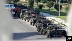 A file photo taken from footage by Sham SNN, a Syrian opposition web channel, shows Syrian army vehicles deployed in the central industrial city of Homs
