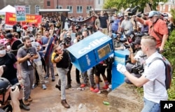 FILE - In this Aug. 12, 2017 file photo, white nationalist demonstrators, right, clash with a counter demonstrator as he throws a newspaper box at the entrance to Lee Park in Charlottesville, Va.