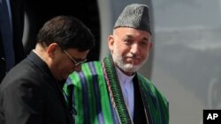 Afghanistan President Hamid Karzai (R) steps off an airplane after arriving in New Delhi, October 4, 2011.