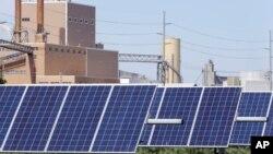 资料照片:内布拉斯加州弗里蒙特的一组太阳能电池板,后面可见一家发电场。(2018年5月31日)