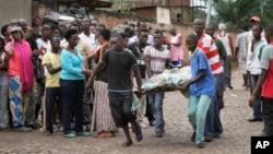 Men carry away a dead body in the Nyakabiga neighborhood of Bujumbura, Burundi, Dec. 12, 2015.