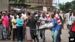 在布隆迪的布琼布拉街头,人们把一具尸体移走。(2015年12月12日)