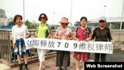 中国维权人士6月12日在北京举牌要求当局释放709律师(参与网图片)