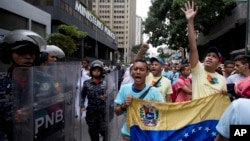 Opposition leader Leocenis Garcia, right, with members of his party, shout slogans against Venezuela's President Nicolas Maduro outside the attorney general's office, where police stand guard, in Caracas, Venezuela, July 18, 2018. The previous night, another opposition leader, Henrique Capriles, called on the country's political forces to reorganize in order to cope with the South American country's hyperinflation, and lack of food and medicine.