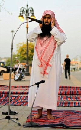 A member of the Committee for the Promotion of Virtue and Prevention of Vice, or religious police, calls for prayers on a street outside coffee shops in Riyadh June 27, 2010.