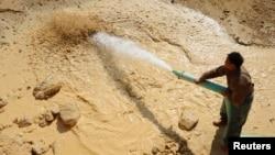 2011年1月16日工人在江西省南城县稀土金属矿场浇水。