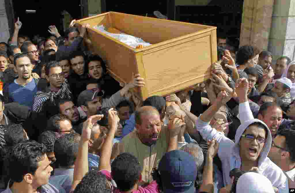 Relatives and colleagues of an Egyptian student who was killed Thursday during clashes with security forces near Cairo University chant slogans as they carry his coffin following Friday prayers in Cairo, Nov. 29, 2013.