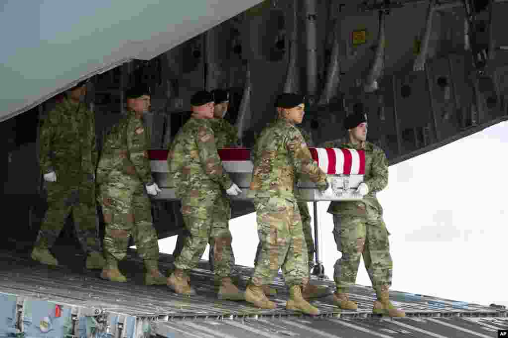 An Army carry team brings homes the remains of Army Sgt. Douglas Riney, 26, of Fairview, Ill., Friday, at Dover Air Force Base, Del. Riney died of wounds received fighting in Afghanistan.