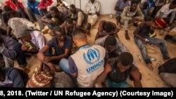 Un agent du HCR au milieu de migrants en Libye, 8 septembre 2018. (Twitter/UN Refugee Agency)