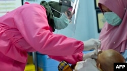 Seorang petugas medis mengenakan baju pelindung memberikan vaksinasi kepada seorang bayi di sebuah puskesmas di Banda Aceh, 18 Mei 2020. (Foto: AFP)