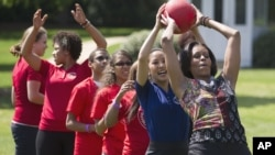 First lady Michelle Obama hands a ball to Olympic skater Michelle Kwan during an event in 2011 to promote physical fitness among military families