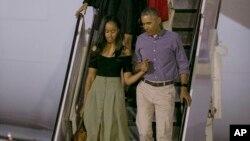 Presiden AS Barack Obama menggandeng putrinya Sasha, diikuti istrinya Michelle dan putrinya Malia, menuruni pesawat Air Force One setibanya di Honolulu untuk liburan tahunan mereka (16/12). (AP/Marco Garcia)