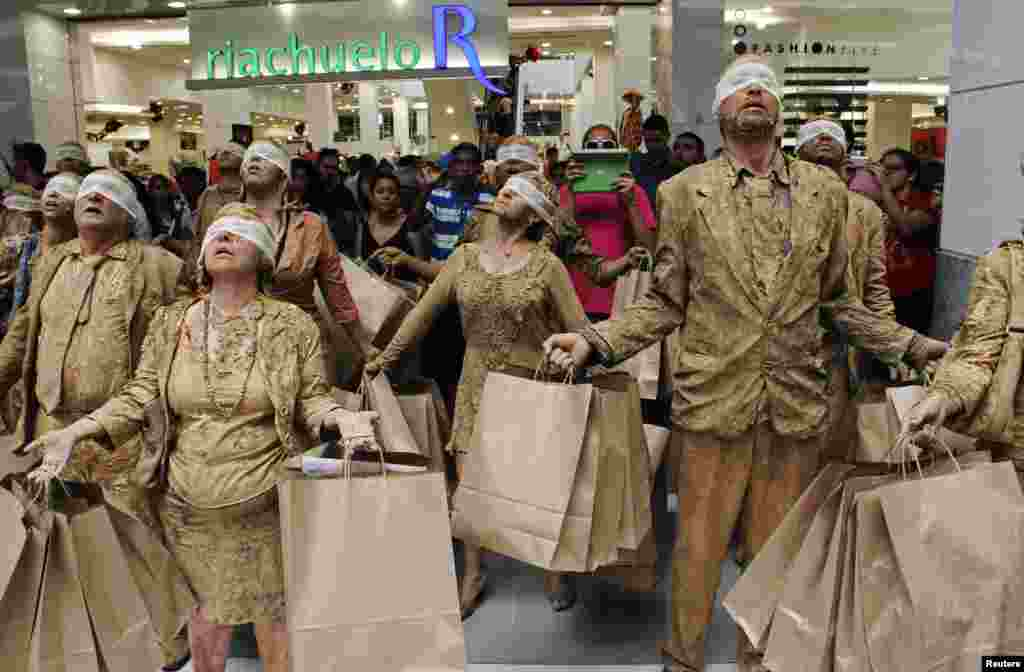 """Students from the School of Communication and Art of the University of Sao Paulo perform a skit titled """"Blind Ones"""" as a protest against consumerism inside a shopping mall of Natal, capital of Rio Grande do Norte state, Brazil, Dec. 9, 2013."""
