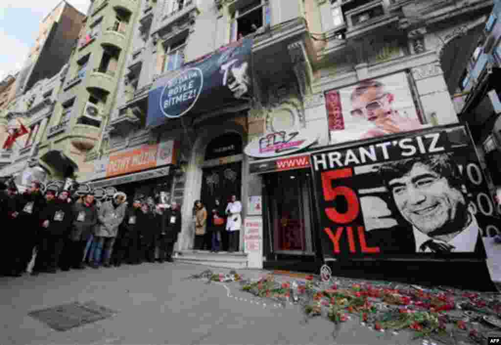 Friends stand outside his office as tens of thousands of protesters march to mark the fifth anniversary of Turkish-Armenian journalist Hrant Dink's murder in Istanbul, Turkey, Thursday, Jan. 19, 2012, as outrage continues to grow over a trial that failed