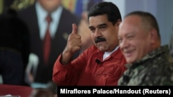 FILE - Venezuela's President Nicolas Maduro gestures during a TV show with National Constituent Assembly member Diosdado Cabello in Caracas, Venezuela, April 11, 2018.