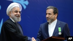 Iranian President Hassan Rouhani, left, shakes hand with Iran's deputy Foreign Minister and senior nuclear negotiator Abbas Araghchi after awarding him a medal of honor in a ceremony in Tehran, Iran, Feb. 8, 2016.