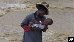A man carries a child while wading across a flooded street during the passing of Hurricane Tomas in Leogane, Haiti, 05 Nov 2010