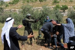 An Israeli soldier points his pistol at a group of Palestinians gathering around a wounded Osama Hajahjeh, 16, near the village of Tekoa, West Bank, Apri 18, 2019.