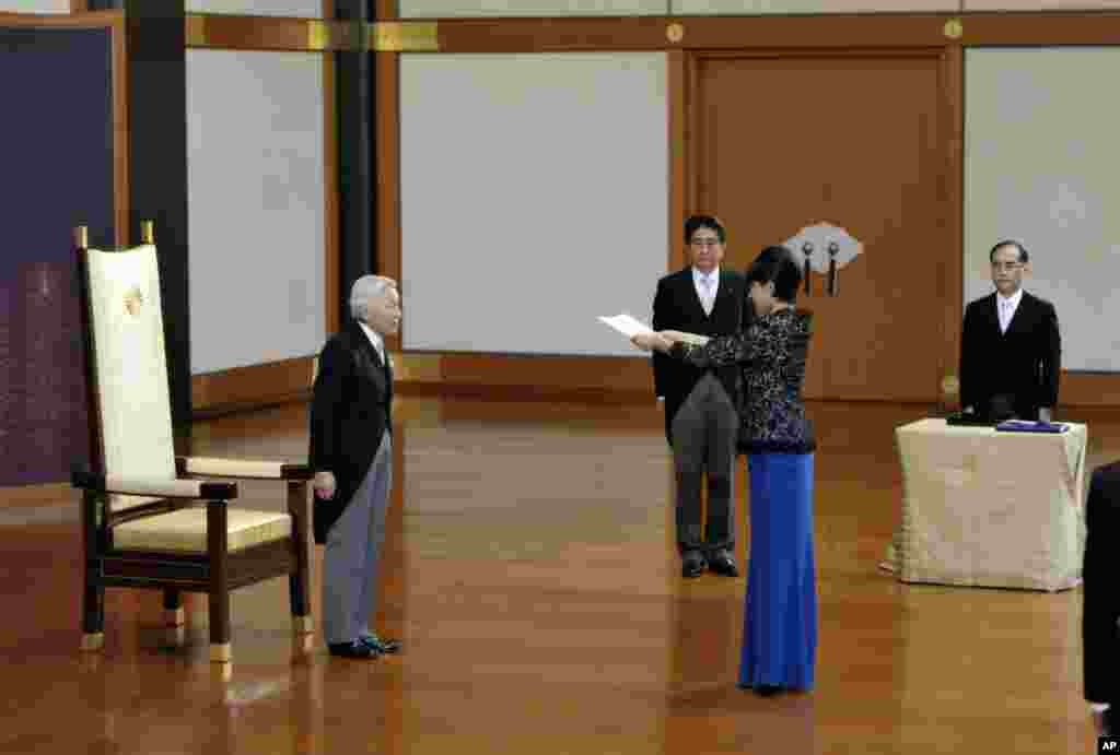 Japanese Emperor Akihito (left) accompanied by Prime Minister Shinzo Abe (second left) stands as newly-appointed Trade and Economy Minister Yuko Obuchi, second right, receives a attestation certificate during a ceremony at the Imperial Palace, in Tokyo, Sept. 3, 2014.