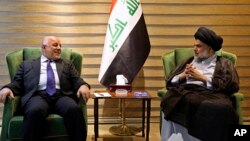 In this photo provided by the Iraqi government, Iraqi Prime Minister Haider al-Abadi, left, meets with Shi'ite cleric Muqtada al-Sadr in the heavily fortified Green Zone in Baghdad, May 20, 2018.