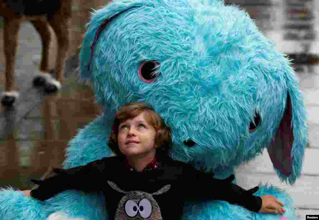 Winston Bartlett, 9, poses for a photograph with a huge Scruff-a-luvs toy at Hamleys store, ahead of announcing their top 10 Christmas toys, in London, Britain.