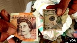 Sobekan uang kertas bergambar Ratu Elizabeth dan George Washington, ditemukan Saji saat memilah sampah plastik di depan rumahnya (foto: Petrus Riski/VOA)