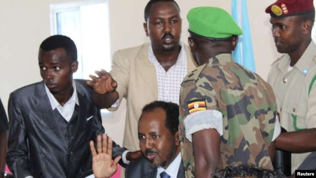 Somalia's newly elected President Hassan Sheikh Mohamud gestures, surrounded by his security guards, during a news conference at Jazeera Palace hotel in Mogadishu September 12, 2012.