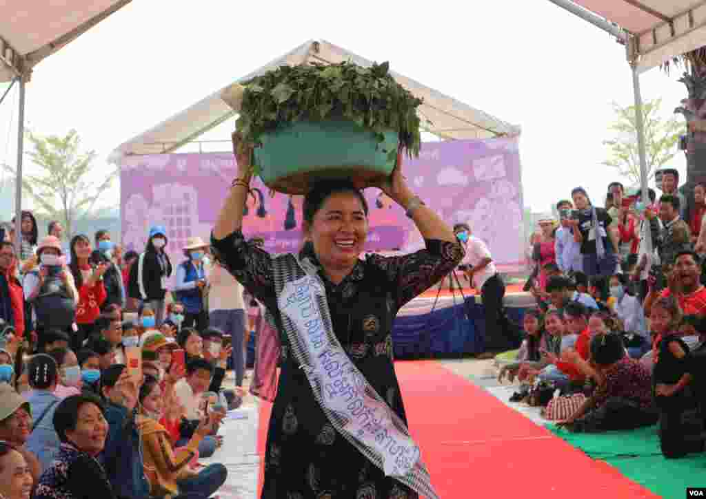 A woman perform fashion show with slogans to promote respect for women's rights as groups of citizens, workers, and civil society representatives celebrate the 109th International Women Rights Day at Freedom Park in March 8, 2020. (Kann Vicheika/VOA Khmer)