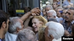 A pensioner (C) reacts as she tries to enter a National Bank branch to receive part of her pension at the city of Iraklio in the island of Crete, Greece July 9, 2015. A race to save Greece from bankruptcy and keep it in the euro gathered pace on Wednesday