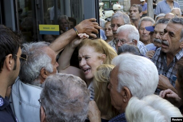 A pensioner (C) reacts as she tries to enter a National Bank branch to receive part of her pension at the city of Iraklio in the island of Crete, Greece July 9, 2015.